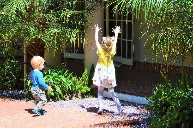 Дети играют лепестками глицинии
