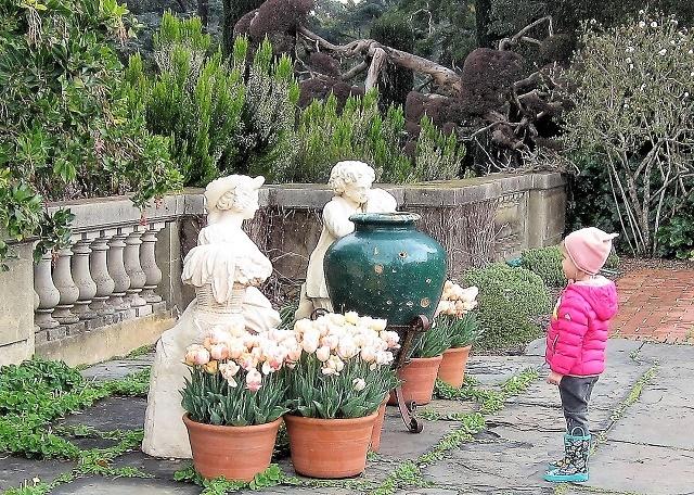 Девочка рассматривает цветы в саду Филоли
